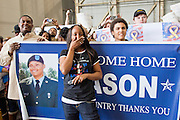 "15 JANUARY 2012 - PHOENIX, AZ:    Family members react as homecoming soldiers march into the hangar at the The 161st Air Refueling Wing of the Arizona Air National Guard in Phoenix. About 100 soldiers of A (Alpha) Company of the 422nd Expeditionary Signal Battalion (referred to as ""Alpha 4-2-2"") of the Arizona Army National Guard returned to Arizona on Sunday, Jan. 15, following a nearly year-long deployment to Afghanistan. More than 10,000 Arizona Army and Air National Guard Soldiers and Airmen have been ordered to federal active duty in support of Operations Noble Eagle, Enduring Freedom, Iraqi Freedom, and New Dawn since September 2001. Approximately 200 Arizona National Guard Soldiers and Airmen are still serving on federal active duty overseas.  PHOTO BY JACK KURTZ"
