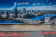 Aerosol writing on the pavement beneath a marketing billboard for new construction in south London. Written on the pavement are the words Sub and Station indicating the future location for some kind of electrical point for powering nearby properties. The poster shows us a London for the 21st Century - the Thames river a deeb blue as if a tropical lagoon in the heart of this modern urban sprawl, a capital of Britain and one of the world's most celebrated metropolis.
