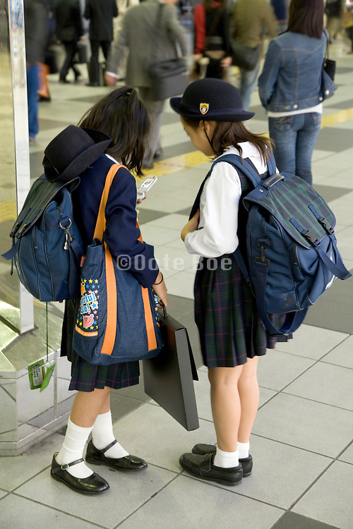 Japanese elementary schoolchildren at a train station checking there cell phone for messages