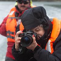 A tourist takes pictures from a zodiac raft in Seno Chico, a fjord in Alberto de Agostini National Park, Tierra del Fuego, Chile.