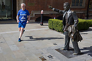 A runner passes-by the sculpture of artist John Seward Johnson, entitled Taxi! 1983 on John Carpenter Street in the City of London, the capitals financial district, on 25th March 2019, in London, England.