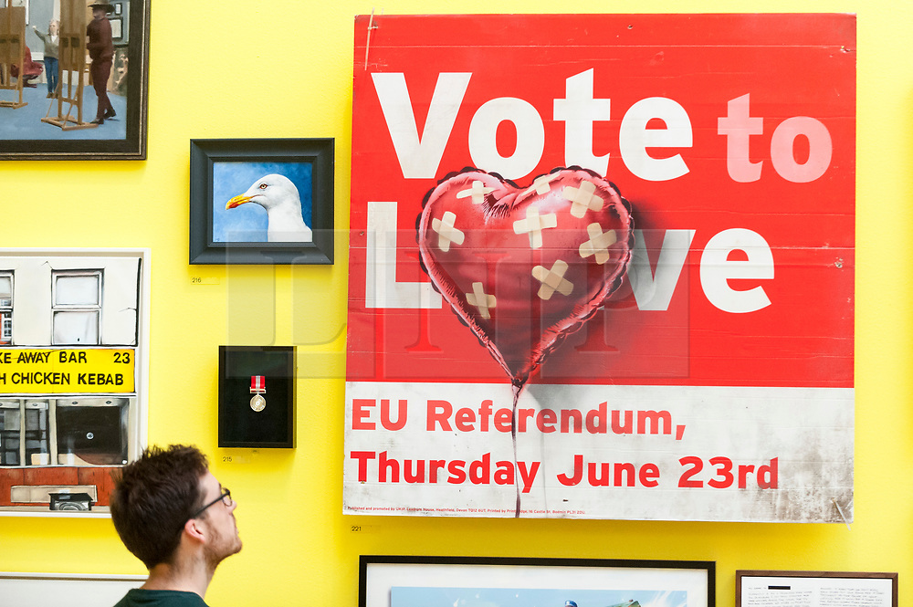"""© Licensed to London News Pictures. 05/06/2018. LONDON, UK. A staff member views """"Vote to Love"""" by Bansky at a preview of the 250th Summer Exhibition at the Royal Academy of Arts in Piccadilly, which has been co-ordinated by Grayson Perry RA this year.  Running concurrently, is The Great Spectacle, featuring highlights from the past 250 years.  Both shows run 12 June to 19 August 2018.  Photo credit: Stephen Chung/LNP"""