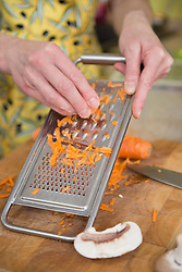 Woman grating carrots in kitchen, close up