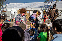 MYTILINI, GREECE - FEBRUARY 09: Volunteers dressed as clowns entertain young refugees inside PIKPA refugee camp set up by volunteers near the official Moria refugee camp on February 09, 2015 in Mytilini, Greece. PIKPA' s mental health and psychosocial support services face the major challenge to provide care for a diverse and transit population. The MHPSS services that they offer include an as broad group of actors as possible who establish the needs for diverse, complementary approaches . For adults, a group of volunteering mental health professionals, offer one to one support. For families and children of the community, psychologists, education, art, music and theatre professionals all work together to offer culturally appropriate, safe and stimulating activities such as art projects, sports and games. The aim is to develop life skills, coping mechanisms and support resiliency and their self confidence. Photo: © Omar Havana. All Rights Are Reserved