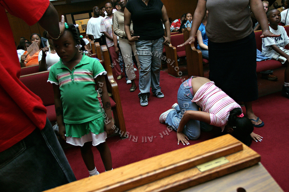 Child being blessed by Rev. Stephen W. Pogue, the Pastor, while a young woman (right) has fell on the floor crying and invoking the Lord, after having being filled by the Holy Spirit, at the Hip Hop Church in Harlem, New York, NY., on Thursday, July 21, 2006. A new growing phenomenon in the United States, and in particular in its most multiethnic city, New York, the Hip Hop Church is the meeting point between Hip Hop and Christianity, a place where ?God? is worshipped not according to religious dogmatisms and rules, but where the ?Holy Spirit? is celebrated by the community through young, unique, passionate Hip Hop lyrics. Its mission is to present the Christian Gospel in a setting that appeals to both, those individuals who are confessed Christians, as well as those who are not regularly attending traditional Services, while helping many youngsters from underprivileged neighbourhoods to feel part of a community, to make them feel loved and to help them not to give up when problems arise. The Hip Hop Church is not only forward-thinking but it also has an important impact where life at times can be difficult and deceiving, and where young people can be easily influenced for the worst purposes. At the Hip Hop Church, members are encouraged to sing, dance and express themselves in any way that the ?Spirit of God? moves them. Honours to students who have overcome adversity, community leaders, church leaders and some of the unsung pioneers of Hip Hop are common at this Church. Here, Hip Hop is the culture, while Jesus is the centre. Services are being mainly in Harlem, where many African Americans live; although the Hip Hop Church is not exclusive and people from any ethnic group are happily accepted and involved with as much enthusiasm. Rev. Ferguson, one of its pioneer founders, has developed ?Hip-Hop Homiletics?, a preaching and worship technique designed to reach the children in their language and highlight their sensibilities, while bringing forth Christianity. This