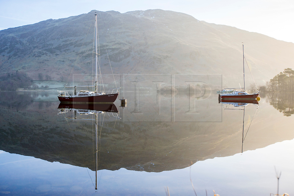 © Licensed to London News Pictures. 21/02/2018. Glenridding UK. Boat's reflect into the calm water of Ullswater lake this morning on a sunny day in Cumbria. Photo credit: Andrew McCaren/LNP