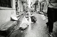 On a busy Hanoi street a Vietnamese woman burns offerings for relatives that have passed away. September in Vietnam, South East Asia.