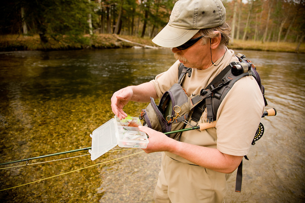 A fly fisherman selects flies to cast to spawning salmon on Michigan's Pere Marquette River.