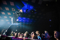 A wide angle shot of Nick Cave at the front of the crowd, Nick Cave and the Bad Seeds, on stage tonight at The Barrowlands, Glasgow, Scotland.<br /> ©Michael Schofield.