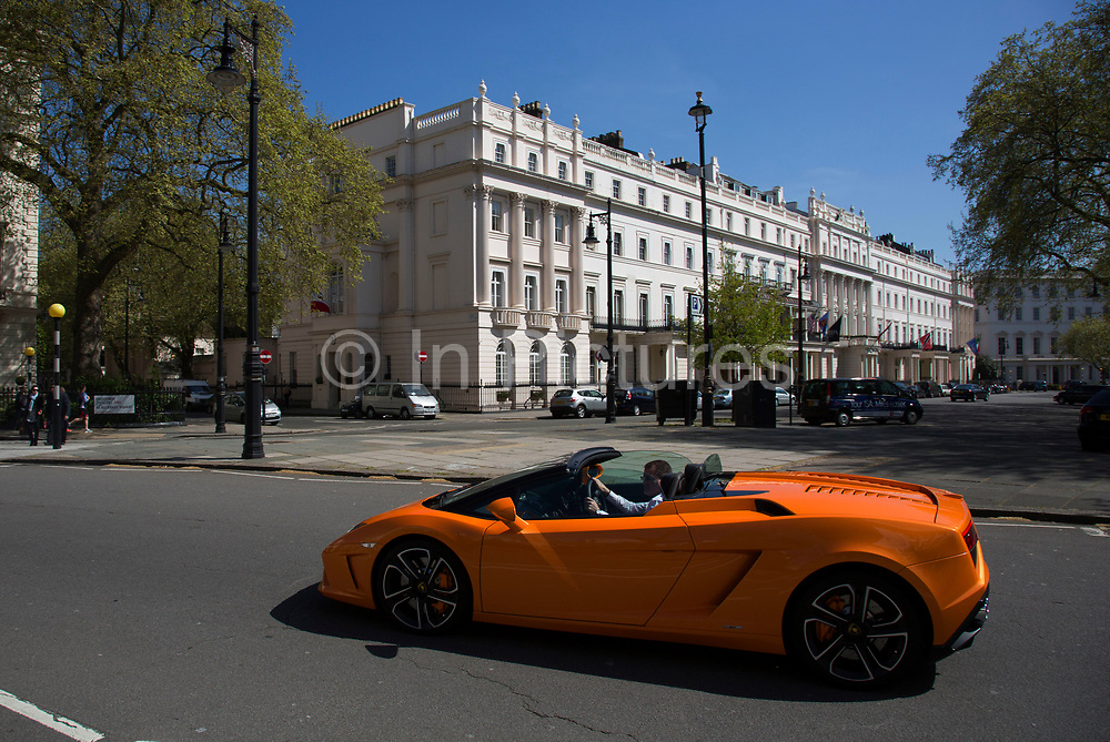 Man driving a Lamborghini Gallardo LP560 through Belgravia. Supercars are a common sight in there parts. In a selected few boroughs of West London, wealth has changed over the last couple of decades. Traditionally wealthy parts of town, have developed into new affluent playgrounds of the super rich. With influxes of foreign money in particular from the Middle-East. The UK capital is home to more multimillionaires than any other city in the world according to recent figures. Boasting a staggering 4,224 'ultra-high net worth' residents - people with a net worth of more than $30million, or £19.2million.. London, England, UK.