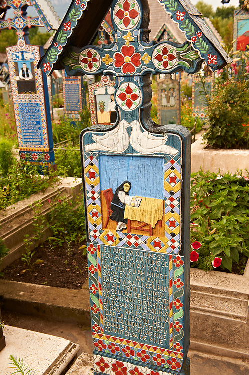 Tombstone showing an aold women sitting at her table,  The  Merry Cemetery ( Cimitirul Vesel ),  Săpânţa, Maramares, Northern Transylvania, Romania.  The naive folk art style of the tombstones created by woodcarver  Stan Ioan Pătraş (1909 - 1977) who created in his lifetime over 700 colourfully painted wooden tombstones with small relief portrait carvings of the deceased or with scenes depicting them at work or play or surprisingly showing the violent accident that killed them. Each tombstone has an inscription about the person, sometimes a light hearted  limerick in Romanian. .<br /> <br /> Visit our ROMANIA HISTORIC PLACXES PHOTO COLLECTIONS for more photos to download or buy as wall art prints https://funkystock.photoshelter.com/gallery-collection/Pictures-Images-of-Romania-Photos-of-Romanian-Historic-Landmark-Sites/C00001TITiQwAdS8