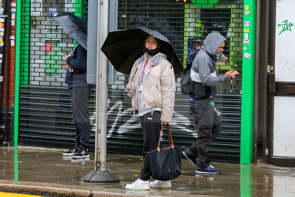 © Licensed to London News Pictures. 21/10/2020. London, UK. Members of the public wearing face coverings shelter from rain underneath umbrellas at a bus stop in north London. According to the Met Office, heavy rain and strong winds are forecast later today from Storm Barbara. Photo credit: Dinendra Haria/LNP