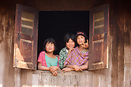 Burmese minority girls smile and gesture out a window in a village near Kalaw, Myanmar.