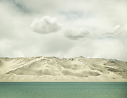 Below puffy clouds, the surreal Pamir mountains, partly wrapped in sand dunes, rise above Bulunkou lake. Shot from the Karakoram Highway, the highest paved road in the world and the only ground transport link between China and Pakistan.