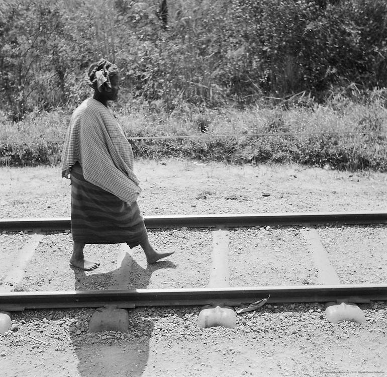 Woman walking on train tracks, Lagos, Nigeria, Africa, 1937