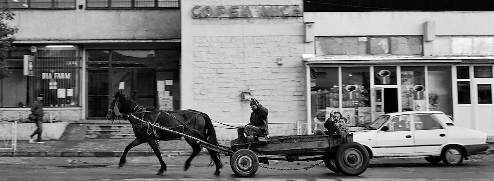 Men pass by in a horse and cart on the main road running through the small Romanian town of Copsa Mica, Transylvania, Romania. Copsa Mica was once described as the most polluted town in Europe. May 9, 2008. Photo Tim Clayton...Copsa Mica, a small industrial town deep in Transylvania, Romania, was described during the 1990s as the most polluted town in Europe with lead levels reaching were more than 1000 times the allowable International limits and life expectancy nine years shorter than the National average...The pollution was caused entirely by two factories, Carbosin produced black for dies and tires and closed in 1993 while Sometra, a nonferrous smelter is still operational today...The pollution was so bad sheep were black, covered in soot and health officials advised against eating livestock or vegetables and drinking the water or milk...The Communist rule of Nicolae Ceausescu is blamed for the widespread environmental degradation that left industrial parts of Romania in ecological disaster. Industry was situated in a way to concentrate pollution in small areas leaving the rest of the country relatively free of pollution.Copsa Mica in particular was left an environmental disaster...The pollution caused a direct affect on human health with widespread Lung disease, Impotency, the highest infant mortality rate in Europe, Lead poisoning andbehavioral problems...Fifteen years on since the closure of Carbosin in 1993, the factory skeleton remains as part of the towns bleak landscape, Unfinished communist style housing blocks still stand in the heart of the towns housing estate. The town's inhabitants arestill trying to recover from the long lasting effects of pollution...Recent survey's found the soil contained so much lead that it was 92 times above the permitted level; the vegetation had a lead content 22 times above the permitted level. While toxins have penetrated at least one meter (three feet) into the soil leaving the entire food chain in