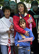 "Elk Grove residents Jan Woods, left; Lee Laudon, center and her daughter Julie Laudon, 9, lower center, joined with others at a ""Support Our Troops"" rally at El Grove Regional Park, Thursday, April 24, 2003.  Speeches by local politicians and members of the military, past and present, were said to give thanks to those who serve and protect   America in time of war.  The American flag was a dominant theme at the rally as people wore and displayed their show of support."