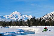 Alaska. Petersville. Mt McKinley (20,320 ft) and snowmachiners.