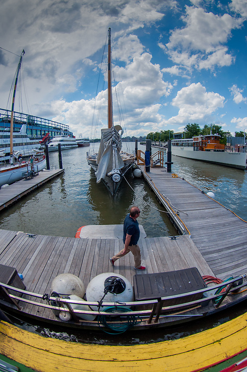 Man Walking and Boats Docked at Chelsea Piers. Hudson River, Manhattan, New York, US