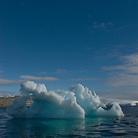 A weathered iceberg drifts in the Neumayer Channel near the Antarctic Peninsula, Antarctica.