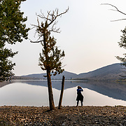 A woman stands on the edge of Convict Lake with binoculars. Wildlife including Eagles, hawks, deer and bear are common around Convict Lake. Signs are also posted throughout the Eastern Sierras to keep an eye out for Bighorn sheep and to report their locations if sighted. Smoke from a nearby wildfire obscures the sky.