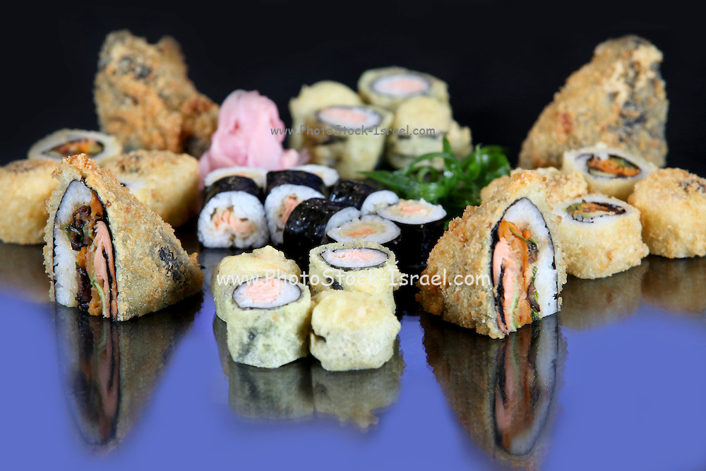 An assortment of various types of sushi including: Sushi Maki, futo maki, Insideout and deep fried sandwich