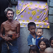THE PHILIPPINES (Manila). 2009. Juanito P. Lyciano, 73, with his game cock in the slumps of the Parola district of Tondo, Manila. Photo Tim Clayton <br /> <br /> Cockfighting, or Sabong as it is know in the Philippines is big business, a multi billion dollar industry, overshadowing Basketball as the number one sport in the country. It is estimated over 5 million Roosters will fight in the smalltime pits and full-blown arenas in a calendar year. TV stations are devoted to the sport where fights can be seen every night of the week while The Philippine economy benefits by more than $1 billion a year from breeding farms employment, selling feed and drugs and of course betting on the fights...As one of the worlds oldest spectator sports dating back 6000 years in Persia (now Iran) and first mentioned in fourth century Greek Texts. It is still practiced in many countries today, particularly in south and Central America and parts of Asia. Cockfighting is now illegal in the USA after Louisiana becoming the final state to outlaw cockfighting in August this year. This has led to an influx of American breeders into the Philippines with these breeders supplying most of the best fighting cocks, with prices for quality blood lines selling from PHP 8000 pesos (US $160) to as high as PHP 120,000 Pesos (US $2400)..