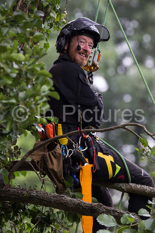 A tree surgeon working with the National Eviction Team prepares to cut an ancient alder tree which environmental activists from HS2 Rebellion had been seeking to protect from works for the HS2 high-speed rail link on 24th July 2020 in Denham, United Kingdom. A large security operation involving officers from the Metropolitan Police, Thames Valley Police, City of London Police and Hampshire Police as well as the National Eviction Team ensured the removal of the tree by HS2 despite the protests by activists.