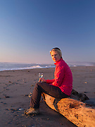 A middle-aged, blonde woman enjoys her glass of white wine while sitting on a drift log, at the beach, Hokitika, New Zealand.
