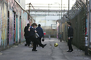 School boys playing football together in the run down area surrounding the old Portsmouth FC ground, UK.