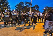 Police in riot gear clash with people protesting against the killing of Alton Sterling on July 10 , 2016. Man pulled from the crowd subdued in cuffs on the street.