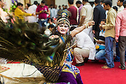 """17 AUGUST 2014 - BANGKOK, THAILAND:  A man dressed as a peacock, which represents the """"Vahana"""" or a bearer of the gods, performs for Krishna Janmashtami in the Vishnu temple in Bangkok. Krishna Janmashtami is the annual celebration of the birth of the Hindu deity Krishna, the eighth avatar of the Hindu god Vishnu. It is celebrated by Hindus in Thailand. There are about 53,000 Hindus in Thailand, most originally from India, but many Hindu deities are highly revered by Thai Buddhists and Hindu holy days are observed by many Thai Buddhists.       PHOTO BY JACK KURTZ"""