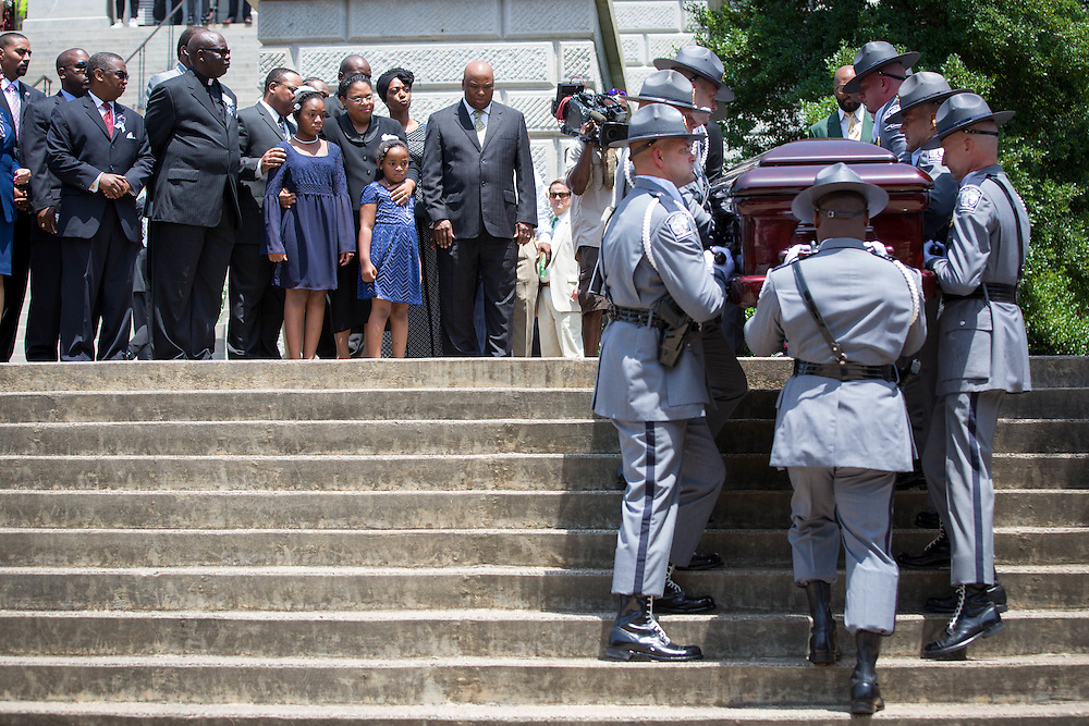The family of Sen. Clementa Pinckney watch as his casket is carried by members of the South Carolina Highway Patrol honor guard carry it up the stopes at the South Carolina Statehouse on June 24, 2015 in Columbia, South Carolina. Photo by Kevin Liles/UPI