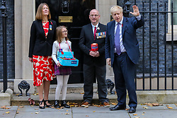 © Licensed to London News Pictures. 28/10/2019. London, UK. The Prime Minister BORIS JOHNSON meets with fundraisers for the Royal British Legion and purchase a poppy in front of No 10 Downing Street door. <br /> Later today MPs will vote on BORIS JOHNSON's motion on a general election on December 2019. Photo credit: Dinendra Haria/LNP