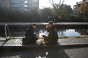 A couple of friends meet by the Regents Canal in Hackney during the second coronavirus national lockdownon on 7th of November 2020, East London, United Kingdom. The canal is home to many living in boats and the canal has become both a home to many and a place to spend time on a sunny day. <br /> The lockdown restrictions mean that people are only allowed to meet outside, in pairs and only if keeping social distance.