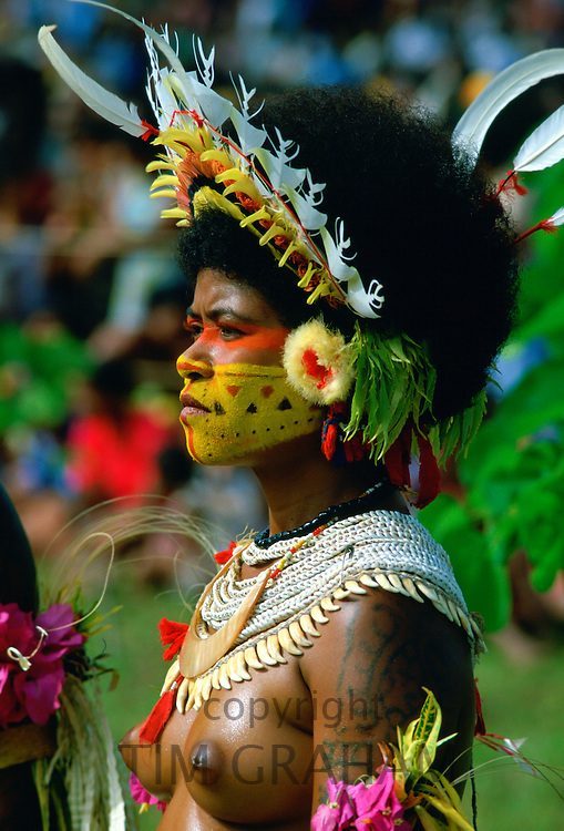 Bare-breasted native woman wearing a feathered headdress, beaded necklaces and face paints during  a gathering of tribes at Mount Hagen in Papua New Guinea