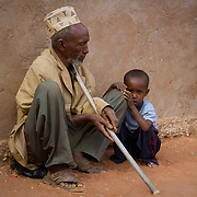 Taking care of his blind grandfather, a small boy waits for their call for relief distribution. Wajir, North Eastern Province, Kenya.