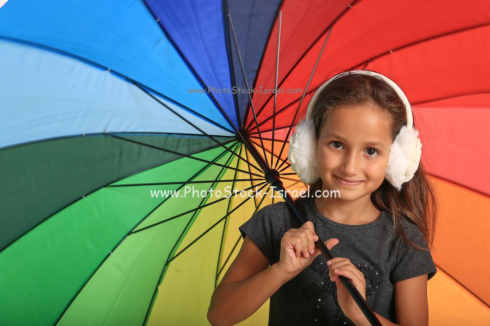 young girl with colourful umbrella and earmuffs