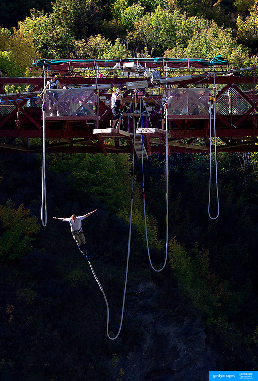 A bungy jumper jumps from The AJ Hackett Kawarau Bridge Bungy Jump, Queenstown New Zealand. The Kawarau Bridge Bungy jump was the World's first Commercial bungy Jump and opened in 1988. The 43m jump attracts tens of thousands of bungy jumpers each year. Queenstown, Central Otago, South Island, New Zealand. 30th March 2011. Photo Tim Clayton.