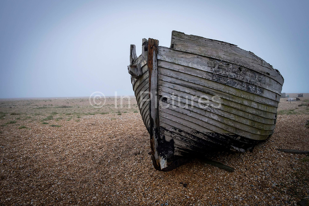 A derelict fishing boat sits on the shingle beach in Dungeness on a misty winters day, on the 25th of January 2020, Dungeness, Kent, United Kingdom. Dungeness is a shingle beach on the coast in Kent, famous for the Dungeness Power Station and Derek Jarman's Prospect Cottage.