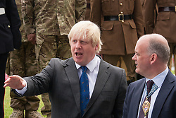 London, June 23rd 2014. Mayor of London Boris Johnson talks to Roger Evans, Chairman of the London Assembly as members and veterans of the armed forces gather at City Hall for a flag raising ceremony to mark Armed Forces Day.