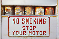 A no smoking stop your motor sign on an old storage bin with old cans of oil in it in Northern Texas.