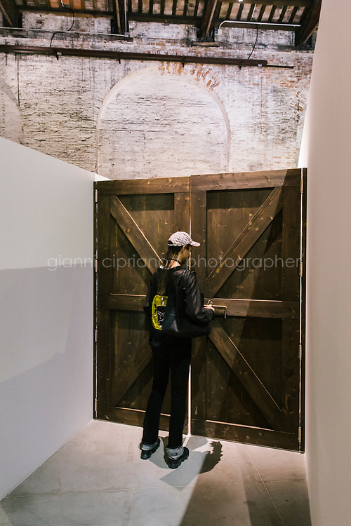 """VENICE, ITALY - 9 MAY 2019: A man opens the door which gives access to """"The Return of the Invisible Woman (also known as 'Visites fantastiques<br /> de Vito Acconci au pays<br /> du fouet')"""" (2014) by Chiara Fumai, is seen here in the exhibition """"Neither Nor: The challenge to the Labyrinth"""", curated by Milovan Farronato, at the Italian Pavilion during the 58th International Art Exhibition of La Biennale di Venezia in Venice, Italy, on May 9th 2019.<br /> <br /> """"Neither Nor: The challenge to the Labyrinth"""" is the title of the exhibition, curated by Milovan Farronato for the Italian Pavilion at the 58th International Art Exhibition of La Biennale di Venezia in which three Italian artists are taking part, presenting completely new works along with ones from the past: Enrico David (Ancona, 1966), Chiara Fumai (Rome, 1978 – Bari, 2017) and Liliana Moro (Milan, 1961).  The subtitle of the project alludes to """"La sfida al labirinto"""" (""""The Challenge to the Labyrinth"""") a seminal essay written by Italo Calvino in 1962 that has been the inspiration for Neither Nor. In this text the author proposes a cultural work open to all possible languages and that feels itself co-responsible in the construction of a world which, having lost its traditional points of reference, no longer asks to be merely represented. To visualize the intricate forms of contemporary reality, Calvino turns to the vivid metaphor of the labyrinth: an apparent maze of lines and tendencies that is in reality constructed on the basis of strict rules. <br /> <br /> The 58th International Art Exhibition of La Biennale di Venezia, titled """"May You Live In Interesting Times"""",is curated by Ralph Rugoff.  The Exhibition is is divided into two separate presentations, Proposition A in the Arsenale and Proposition B in the Giardini's Central Pavilion, comprising 79 artists from all over the world.  """"May You Live In Interesting Times highlights artworks whose forms function in part to call attention to what forms conceal a"""