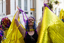 A woman dances along the procession route as day one, Children's Day, of the Notting Hill Carnival gets underway in London. London, August 25 2019.