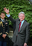 President Bill Clinton smiles and waves after meeting with Yankees owner George M. Steinbrenner III (L) and the team as the 1998 World Series winning Yankees at the White House June 10, 1999 in Washington, DC.