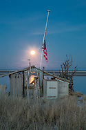 The full snow moon rises over this structure on South Beach, Chatham made from flotsam.