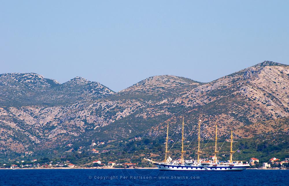 The Peljesac peninsula and Sveti Ilija mountain with a big sailing cruise ship schooner SPV Royal Clipper with five masts on the sea water Korcula Island. Korcula Island. Dalmatian Coast, Croatia, Europe.