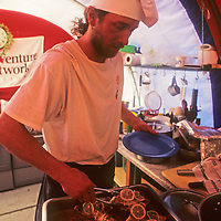 A cook (Michael Holmes) serves fish for dinner in the dining tent at Adventure Network's Patriot Hills expediton base, the first private aviation hub in Antarctica.