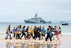 © Licensed to London News Pictures; 11/06/2021; St Ives, Cornwall UK. G7 summit in Cornwall. An XR protest passes along Porthminster Beach with HMS Tamar in the background at a protest by Extinction Rebellion in St Ives on the first day of the G7 summit. Photo credit: Simon Chapman/LNP.