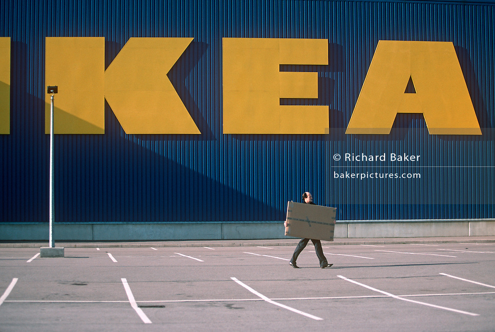 A male customer carries away a flatpacked purchase from Swedish home furnishing store Ikea.
